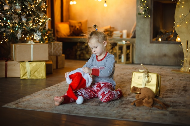 Menina loura pequena da criança nos pijamas do natal que tentam no chapéu de santa que senta-se em casa no tapete. Foto Premium