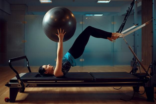 Menina magro em roupas esportivas, pilates treinando com bola na máquina de exercícios no ginásio. Foto Premium