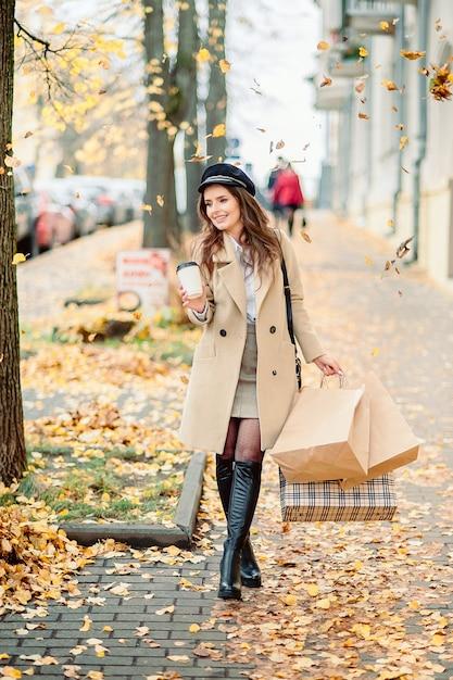 Menina mantém pacotes de artesanato de papel no outono Foto Premium