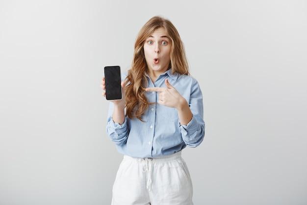 Menina maravilhada com o novo telefone. retrato de jovem europeu chocado e fascinado com cabelo loiro na blusa mostrando smartphone, apontando para o dispositivo, dizendo uau, expressando espanto Foto gratuita