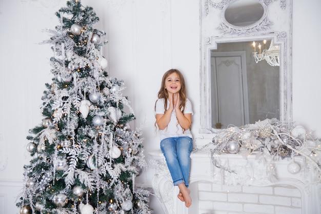 Menina menina que decora a árvore de natal no interior clássico branco, sentado em uma lareira com espelho. feliz natal, feliz ano novo, boas festas. Foto Premium