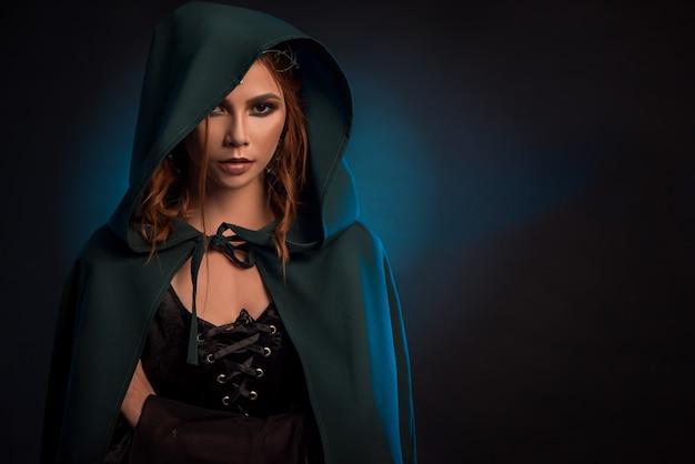Menina místico que levanta no fundo escuro, vestindo o cabo verde, espartilho preto. Foto Premium