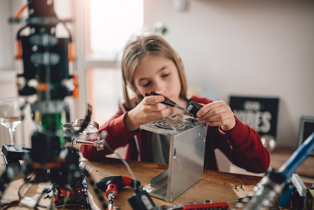 Menina modificando a fonte de alimentação e aprendendo robótica Foto Premium