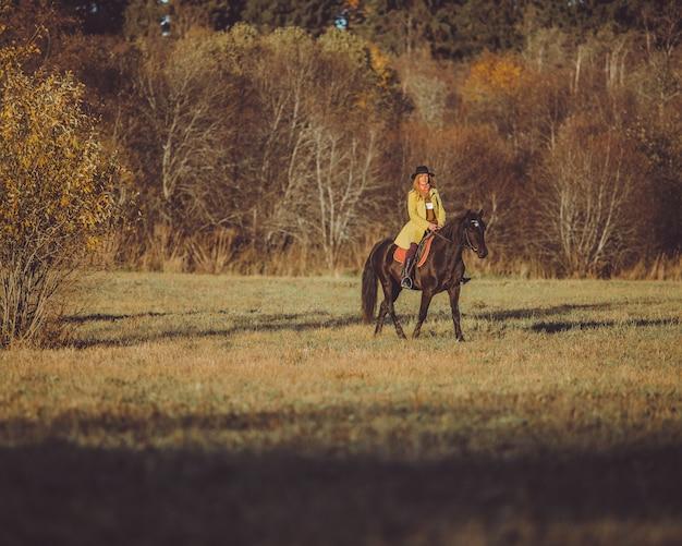 Menina montar um cavalo Foto gratuita