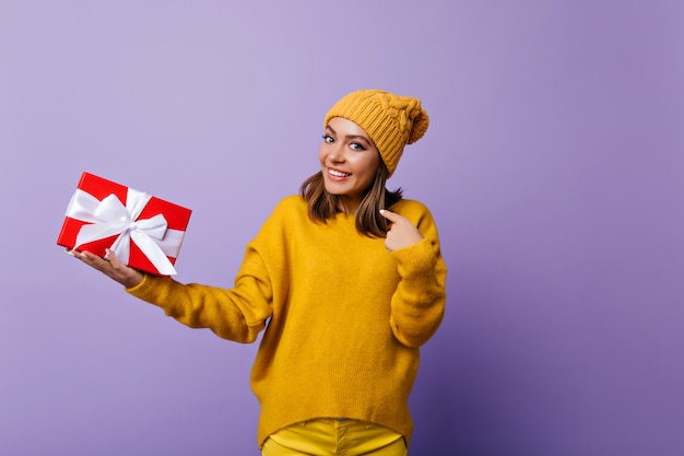 Menina morena animada em um suéter elegante, aproveitando o retratos antes das férias de ano novo. modelo feminino caucasiano em êxtase segurando o presente de aniversário e sorrindo. Foto gratuita