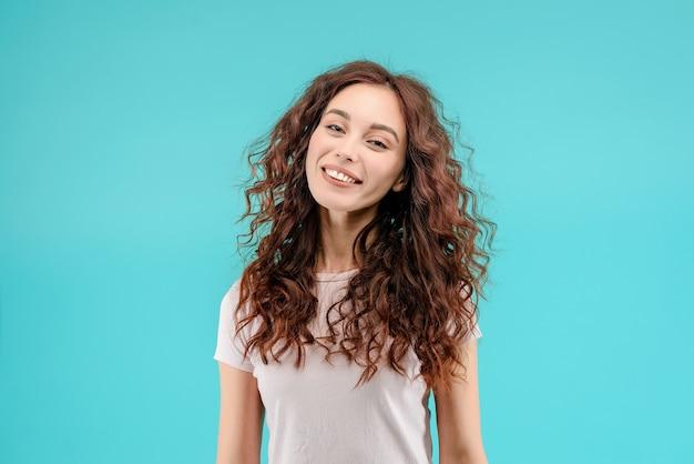 Menina morena atraente com cabelo encaracolado e um sorriso alegre feliz Foto Premium