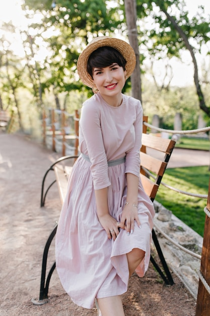 Menina morena atraente e inspirada em um vestido longo e antiquado se passando perto do banco de madeira e sorrindo Foto gratuita