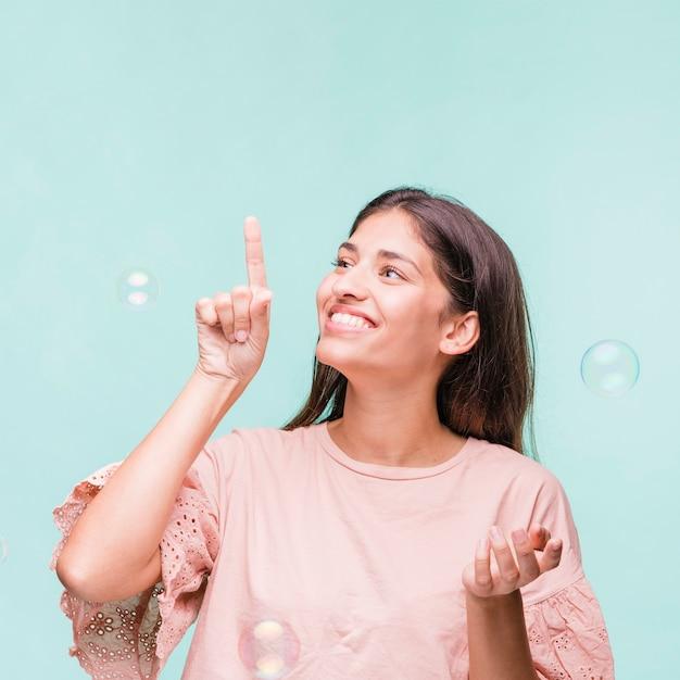 Menina morena brincando com bolhas de sabão Foto gratuita