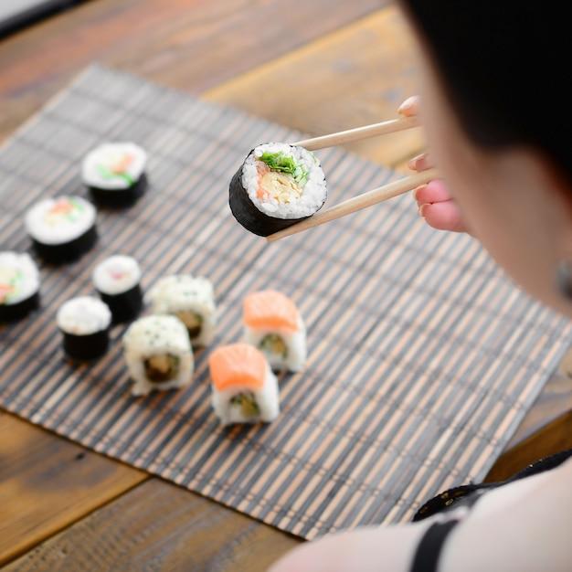Menina morena, com, chopsticks, segura, um, rolo sushi, ligado, um, palha bambu, serwing, esteira, fundo Foto Premium