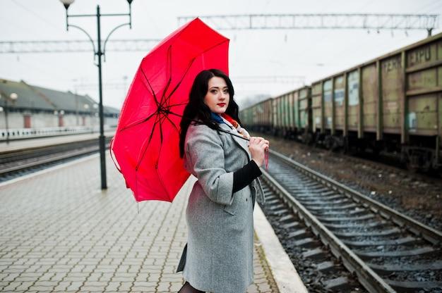 Menina morena de casaco cinza com guarda-chuva rosa na estação ferroviária Foto Premium