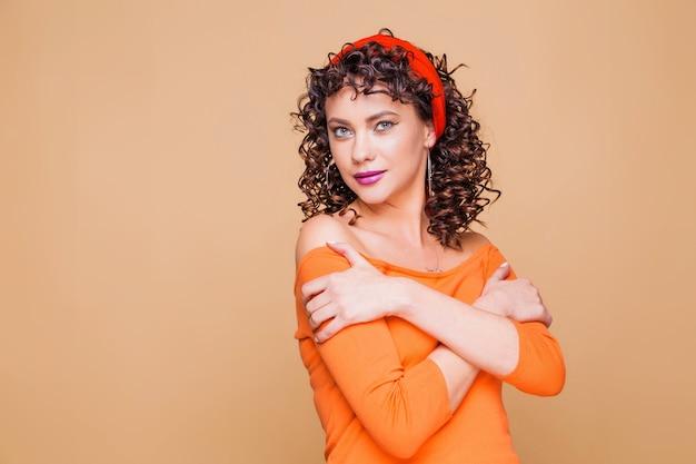 Menina morena elegante com um suéter laranja brilhante e uma bandana posando em laranja Foto Premium