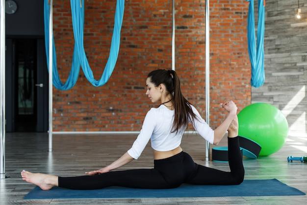 Menina morena em roupas esporte preto e branco faz ioga e alongamento no ginásio Foto gratuita
