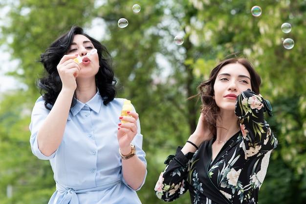 Menina morena fazendo bolhas de sabão com o amigo Foto gratuita