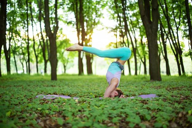 Menina morena fina pratica esportes e executa poses de ioga em um parque de verão no pôr do sol Foto Premium