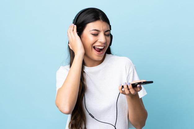Menina morena jovem sobre música de parede azul isolado com um celular e cantando Foto Premium