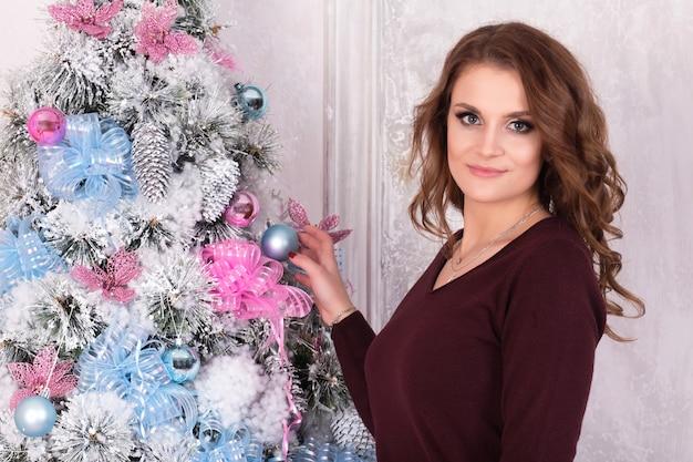 Menina morena linda com um suéter vermelho fica perto de uma árvore no ano novo e sorrindo e segurando uma bola Foto Premium