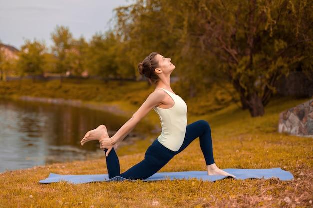 Menina morena magro entra para esportes e realiza poses de ioga no outono na natureza à beira do lago Foto Premium