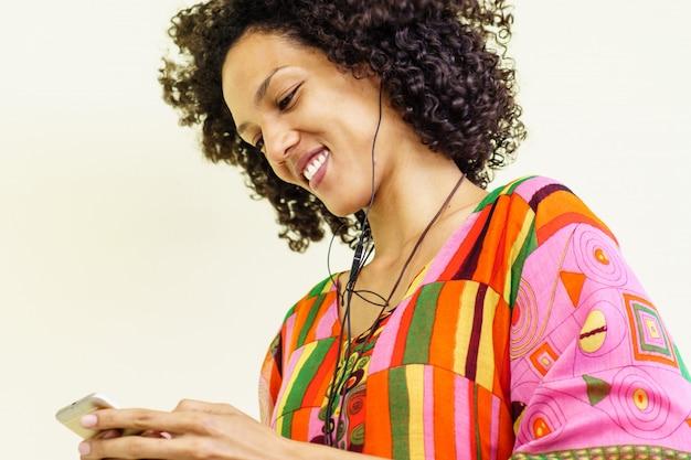 Menina morena ouvindo música com seu telefone celular Foto gratuita