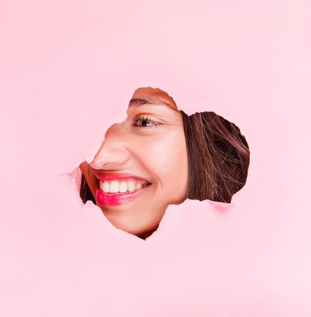 Menina morena posando através de um buraco de papel Foto gratuita
