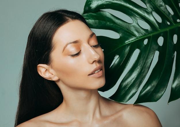 Menina morena posando com folhas exóticas Foto Premium