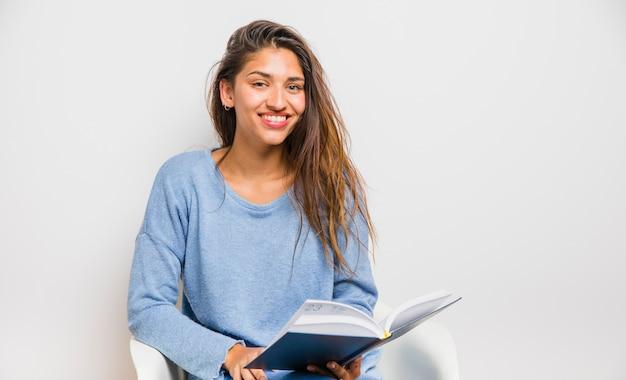 Menina morena sentada lendo um livro Foto gratuita