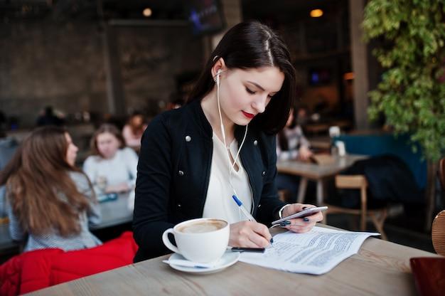 Menina morena sentada no café com uma xícara de cappuccino, ouvindo música em fones de ouvido e escrever alguns documentos. Foto Premium