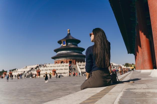 Menina morena sentada nos degraus do templo de heven na china Foto gratuita