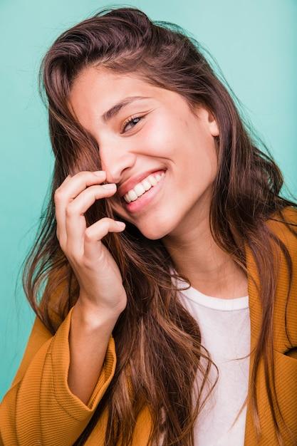Menina morena sorridente posando com casaco Foto gratuita