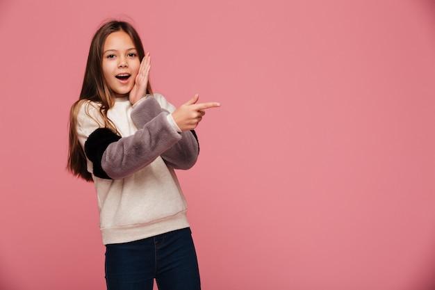 Menina morena surpresa, apontando para o espaço da cópia com a boca aberta isolada Foto gratuita