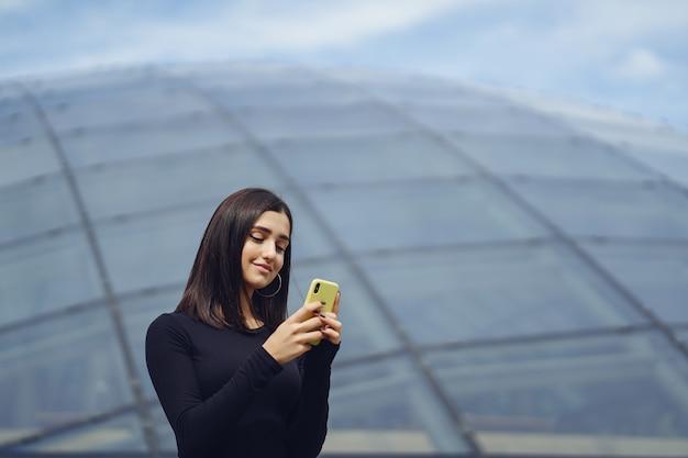 Menina morena usando seu celular enquanto ela está explorando uma nova cidade Foto gratuita