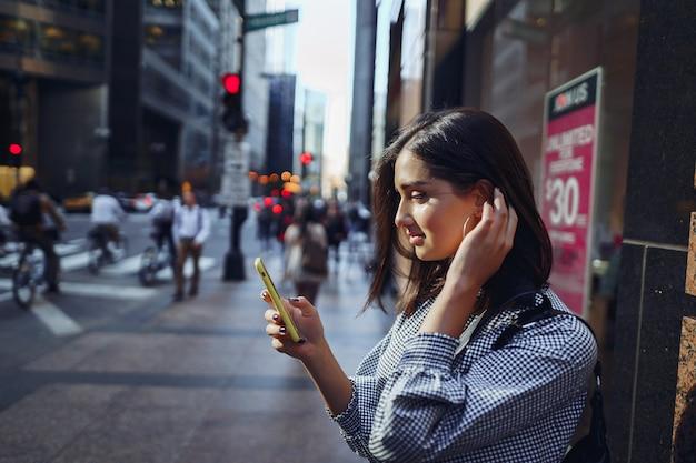 Menina morena usando seu celular para chegar a um amigo Foto gratuita