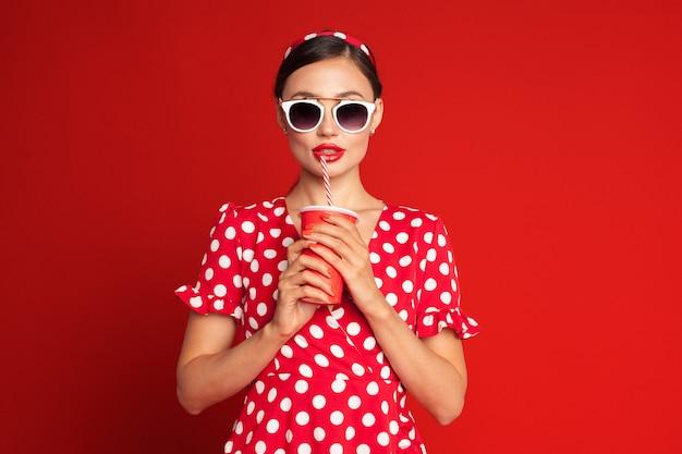 Menina moreno alegre do pin-up que guarda o refresco Foto Premium