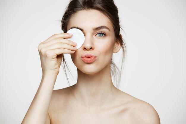 Menina moreno bonita com o olho escondido da pele perfeita limpa atrás da esponja do algodão que sorri olhando a câmera sobre o fundo branco. cosmetologia e spa. Foto gratuita