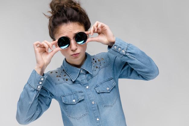 Menina moreno nova em vidros redondos os cabelos estão reunidos em um coque. a garota continua ajeitando os óculos. Foto Premium