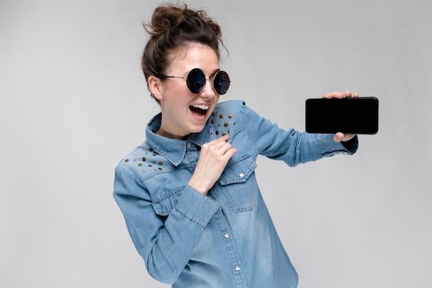Menina moreno nova em vidros redondos os cabelos estão reunidos em um coque. menina com um telefone preto. Foto Premium