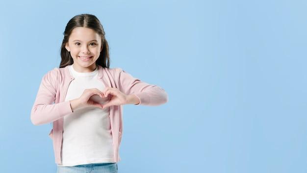Menina, mostrando, coração, sinal, em, estúdio Foto Premium