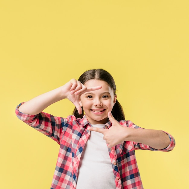 Menina, mostrando, dedo, quadro, em, estúdio Foto gratuita