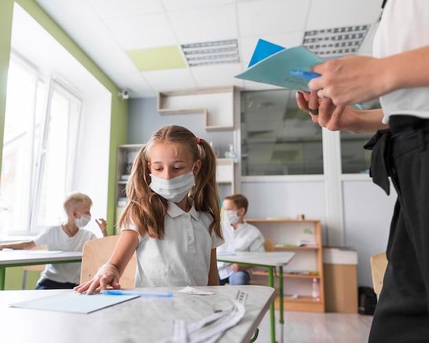 Menina mostrando seu dever de casa para a professora Foto Premium
