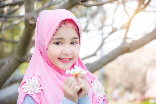 Menina muçulmana bonita que está sob uma árvore e que guarda a flor branca com sorrisos. Foto Premium
