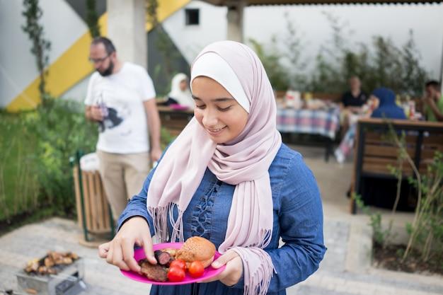 Menina muçulmana com hijab comendo comida de churrasco Foto Premium
