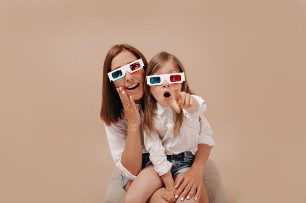Menina muito charmosa com a mãe assistindo a um filme com óculos 3d e mostrando um ponto para a câmera Foto gratuita