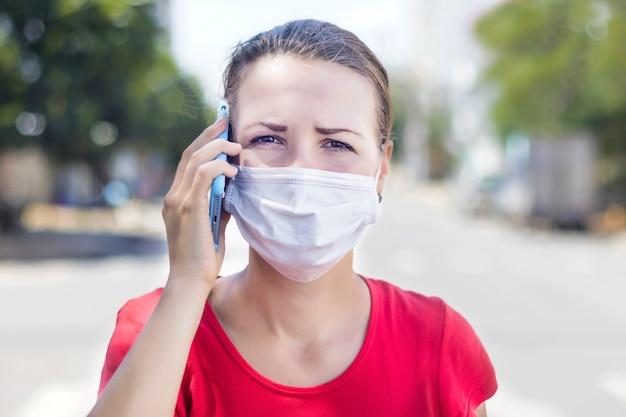 Menina, mulher ansiosa na máscara médica estéril protetora no rosto chamando ambulância, falando no celular ao ar livre na rua asiática. poluição do ar, vírus, conceito de pandemia de coronavírus chinês Foto Premium