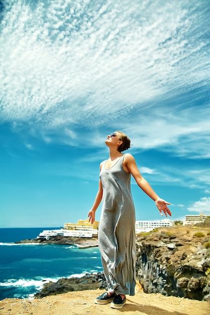 Menina mulher em roupas casuais hipster em pé no penhasco da montanha Foto gratuita