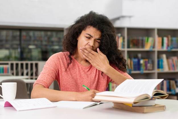 Menina na biblioteca, sentindo-se sonolento Foto gratuita