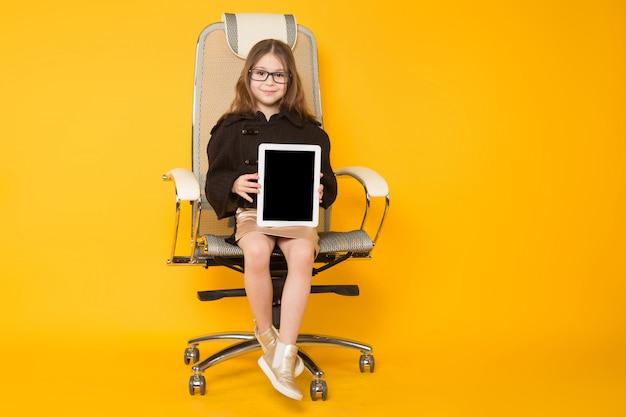 Menina na cadeira com computador tablet Foto Premium