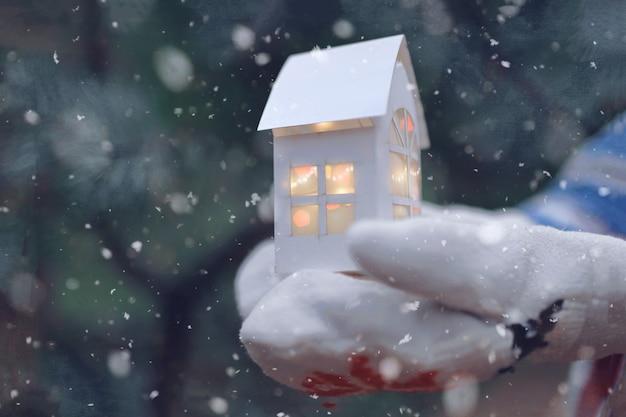 Menina na luva, segurando uma casa de papel com luz de natal Foto Premium