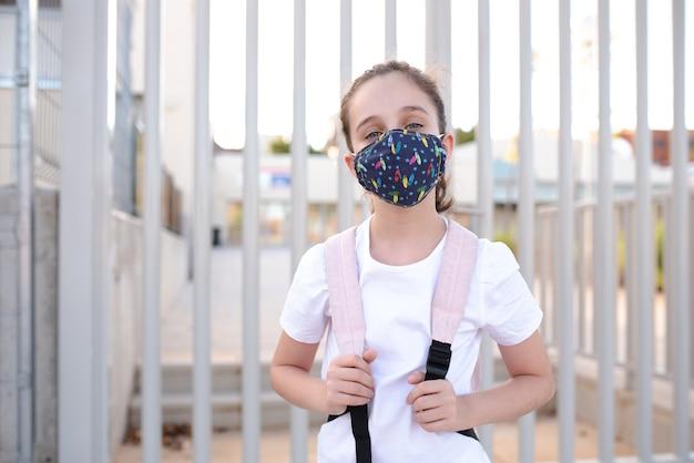 Menina na porta da escola com máscara no novo normal Foto Premium