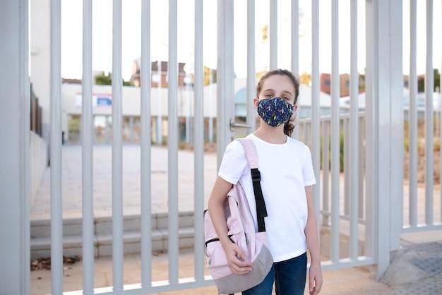 Menina na porta da escola com máscara Foto Premium