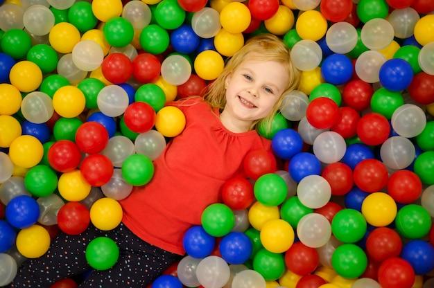 Menina na vista superior do poço de bola Foto gratuita