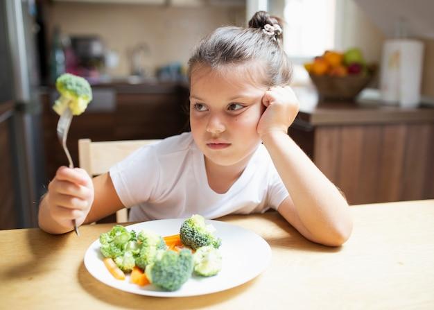 Menina não está feliz com legumes em casa Foto gratuita